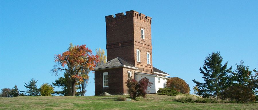 Alexander's Castle sit at Fort Worden Historical State Park is flanked by trees with autumn-colored leaves