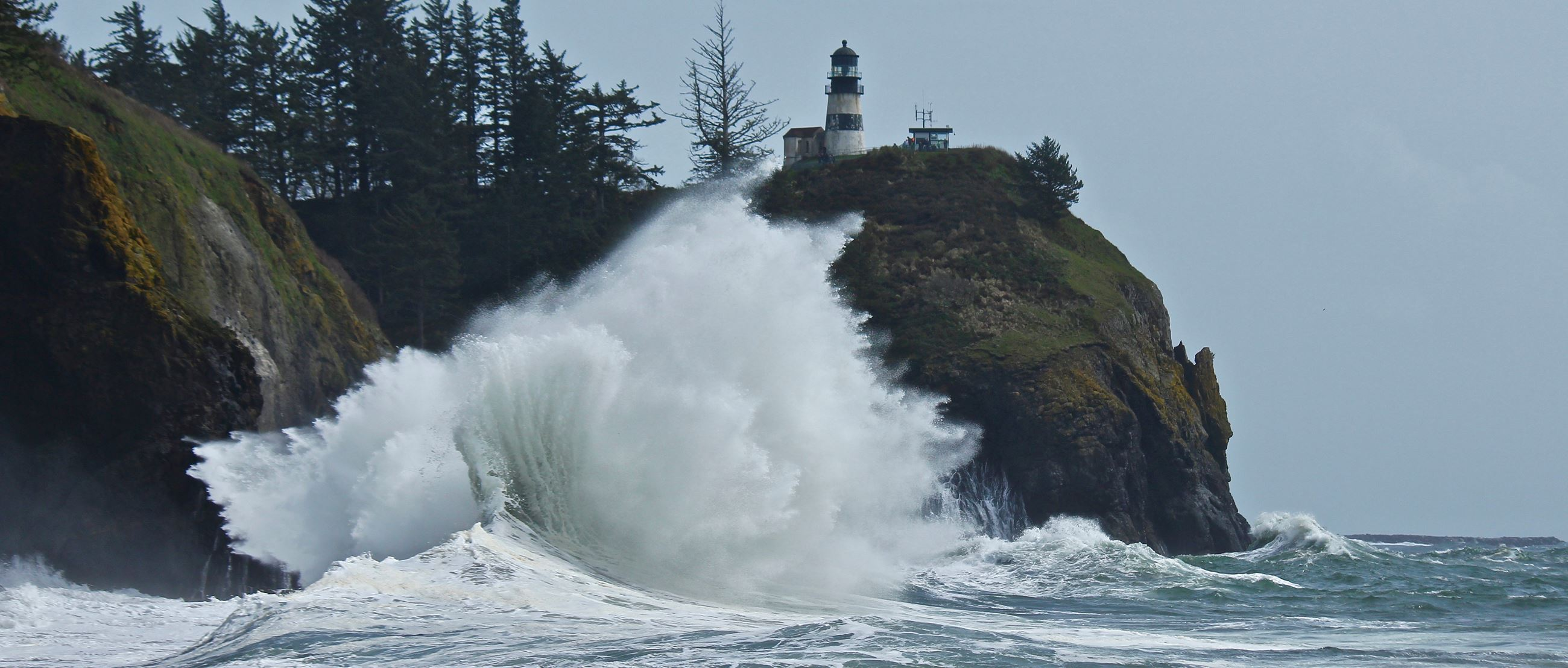 Waves crash dramatically against the cliffs at Cape Disappointment State Park