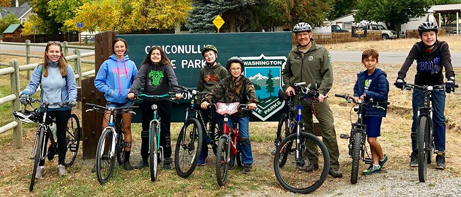 Riders and a park ranger pose before Conconully State Park's sign during a 2018 Bike Your Park Day event