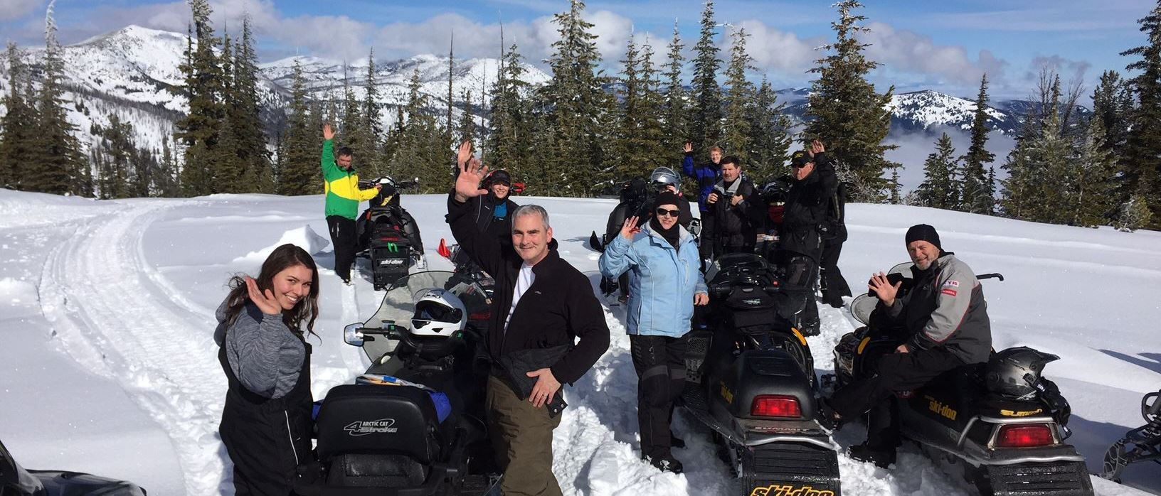 A group of snowmobilers waves from the top of a snow-covered peak near Marble Mountain