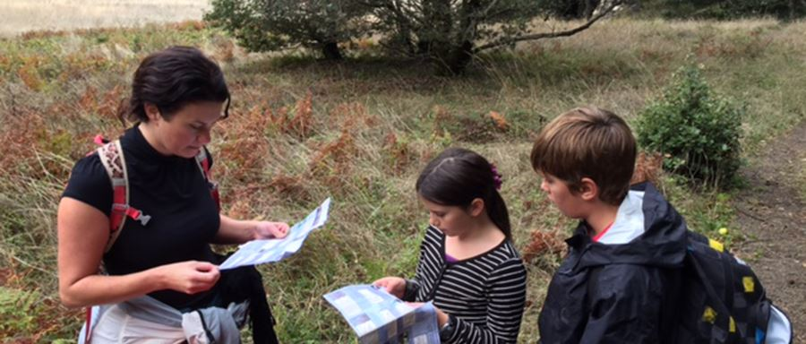 A woman and three children in backpacks intently examine scavenger hunt instructions on paper. They are standing on dry grass with a small shrub-like tree in the background.